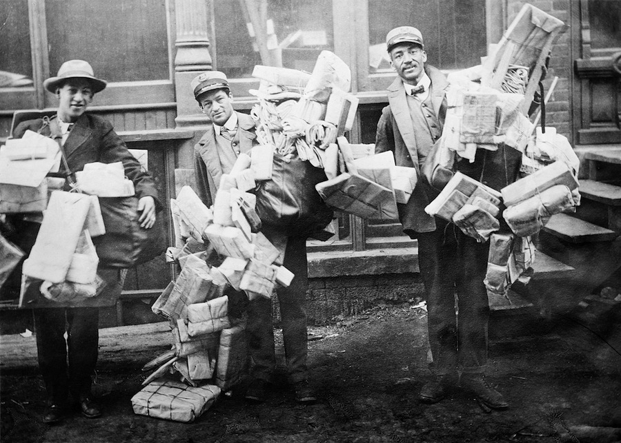 Mail carriers loaded with Christmas mail. Credit: Library of Congress.