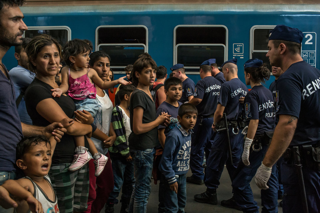 A migrant family faced police officers at the Keleti train station in Budapest. Credit: Mauricio Lima for The New York Times.