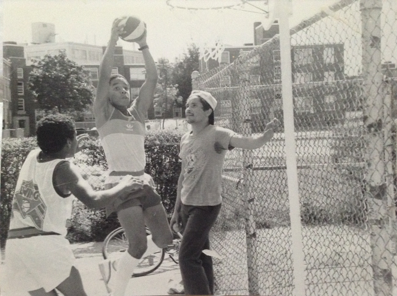 Tico Garcia (left) plays basketball with his twin, Daco Garcia, as Rainier Rosado looks on.